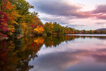 El follaje de otoño refleja en Hesse en el lago al atardecer, cerca de Bear Mountain, Nueva York