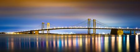 デラウェア記念橋夜、ニュージャージーから見た。デラウェア記念橋はニュージャージー州とデラウェア州のデラウェア州川を渡る双子吊橋のセッ 写真素材