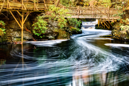 meanders: Little Bushkill creek meanders through the forest and leaves long exposure foam trails under wooden bridges. Bushkill Creek is a tributary of the Delaware River in eastern Pennsylvania