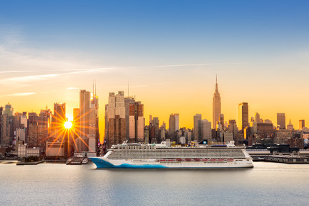 cruise: New York City skyline at sunrise, as viewed from Weehawken, along the 42nd street canyon. A large cruise ship sails Hudson river, while sun beams burst between the skyscrapers.