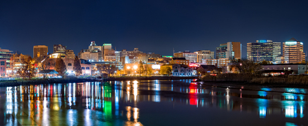 Wilmington skyline panorama by night, reflected in Christiana River. Wilmington is the largest city in the state of Delaware. Stock Photo