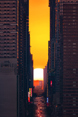 42nd: Sunrise Manhattanhenge in New York City, along the 42nd street. Manhattanhenge is an event during which the sun is aligned with the main street grid of Manhattan, New York City Stock Photo