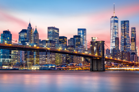 Brooklyn Bridge at and the Lower Manhattan skyline under a purple sunset