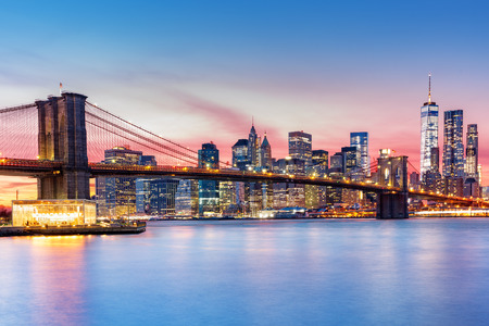 architecture and buildings: Brooklyn Bridge and the Lower Manhattan skyline under a purple sunset Stock Photo