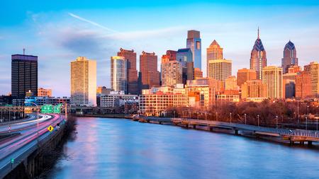 フィラデルフィアの夕方。 スカイラインは、オレンジ色の夕日光の下で点灯します。スクールキル高速道路スクールキル川と平行に走っています。