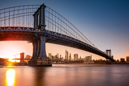 enhances: Manhattan Bridge framing New York skyline at sunset. The use of a fisheye effect enhances the perspective. Stock Photo