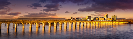 Philadelphia and Reading Railroad Bridge crosses Susquehanna river at sunset. Harrisburg skyline shines under a late afternoon light. Stockfoto
