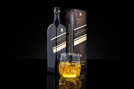 Fles, doos en glas van Johnnie Walker Double Black blended Scotch whisky. Johnnie Walker is de meest verspreide merk van blended Scotch whisky in de wereld.