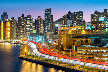 夕暮れ時、マンハッタン、ニューヨーク市で FDR ドライブのラッシュアワーの交通渋滞で東のハーレム近所スカイライン 写真素材