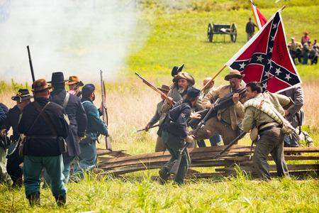 gettysburg battlefield: Confederate soldiers breach an union barricade during the Battle of Gettysburg reenactment.