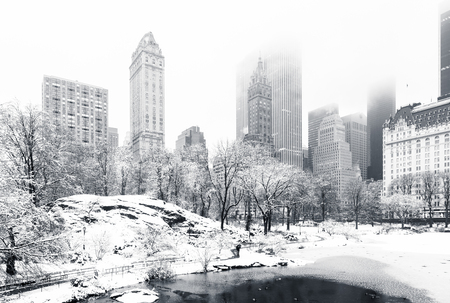 The Pond in Central Park on a foggy winter morning, as viewed from Gapstow Bridge. Low clouds cover Manhattan skyscrapers