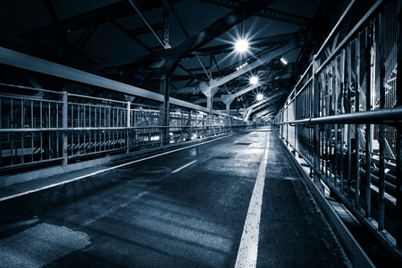 Moody monochrome view of Williamsburg bridge pedestrian walkway by night in New York City Banco de Imagens