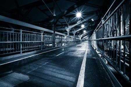 industry moody: Moody monochrome view of Williamsburg bridge pedestrian walkway by night in New York City Stock Photo