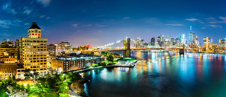 boroughs: New York City panorama by night. Brooklyn Bridge spans East River linking Manhattan and Brooklyn boroughs