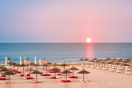 Clear sky sunrise over a sandy Black Sea beach, with straw umbrellas, in Romania