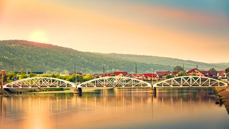 Jiu-brug in Targu Jiu, Roemenië. De oude brug, gebouwd in 1896, is verplaatst naar het noorden van zijn oorspronkelijke locatie, om Central park te verbinden met een kunstmatig eiland