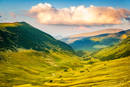 sheepfold: Valley along the mountain peaks crossed by Transalpina road, at Urdele pass, in Valcea county, Romania Stock Photo