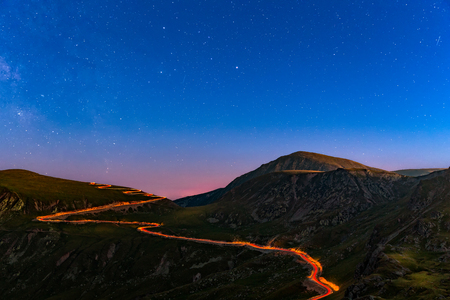 Transalpina road under a starry night with traffic trails along the winding road. Transalpina is one of the highest roads passing the Carpathians in Romania.