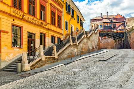 Cobblestone street passes under The Bridge of Lies, a landmark of the old town of Sibiu, Romania