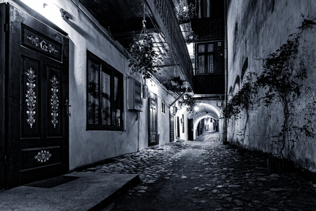 gritty: Moody monochrome view of a cobblestone street passage in the old city center of Sibiu, Romania Stock Photo