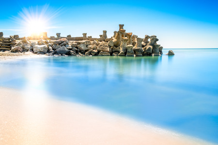 beach landscape: Long exposure scene with Sunrise above a beach breakwater structure, in Gura Portitei Black Sea resort, Romania