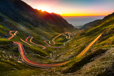 Sentiers de la circulation sur Transfagarasan passent au coucher du soleil. Traversée de montagnes des Carpates en Roumanie, Transfagarasan est l'une des routes de montagne les plus spectaculaires du monde. Banque d'images - 64612907