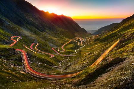 Verkeer paden op Transfagarasan doorgeven bij zonsondergang. De kruising van de Karpaten in Roemenië, Transfagarasan is een van de meest spectaculaire bergwegen in de wereld. Stockfoto - 64612907