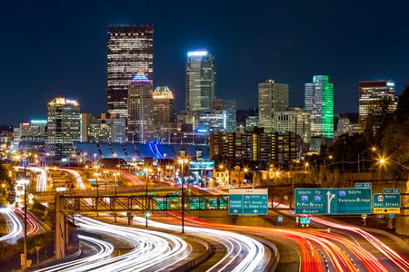 'S nachts de horizon van Pittsburgh. Het spitsuurverkeer verlaat lichte paden op de I-279 Parkway