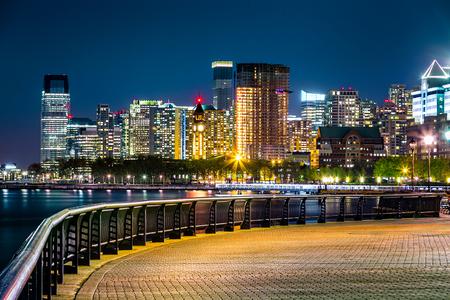 Jersey City skyline by night along Hudson river promenade. Stock Photo