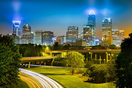 Traffic light trails in Charlotte, North Carolina. The city skyline glows on a foggy night. Stock Photo