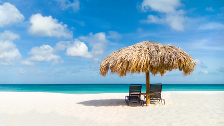 Straw umbrella on Eagle Beach, Aruba on a lovely summer day Banco de Imagens