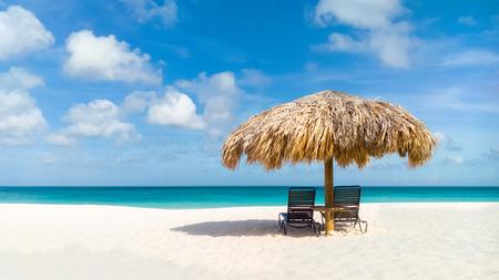 Straw umbrella on Eagle Beach, Aruba on a lovely summer day Standard-Bild