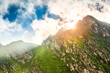 Zongloed barstend achter een bergpiek langs Transfagarasan-pas, in Roemenië Stockfoto