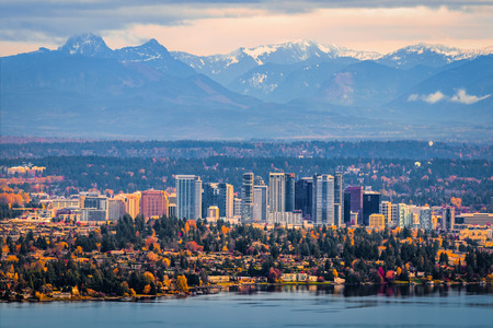 Bellevue Washington. The snowy Alpine Lakes Wilderness mountain peaks rise behind the urban skyline. Banco de Imagens