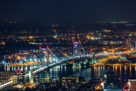 Aerial view of Ben Franklin Bridge by night spanning Delaware river, in Philadelphia