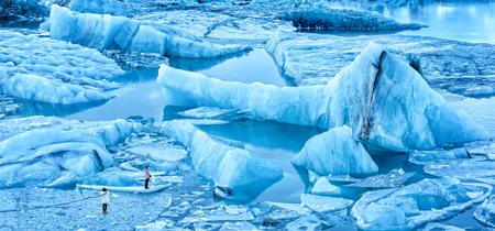 Jokulsarlon glacier lagoon panorama at dawn, in Iceland. Unidentifiable tourists walk on thin ice to photograph spectacular icebergs. Stock Photo