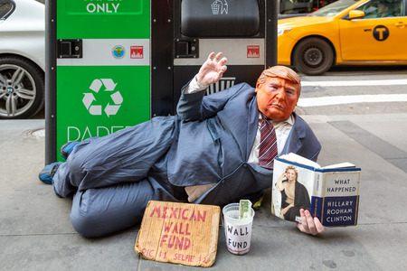 NEW YORK -  MAY 3, 2018: Funny street beggar wears a Trump mask and a dirty businessman suit. The man mocks the current American president and asks tourists for money to fund the Mexican border wall. Editorial