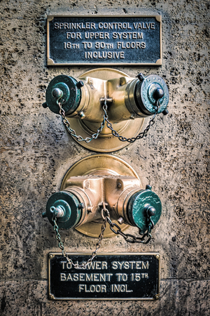 Generic golden wall sprinkler connection in New York City (grunge processing) Banque d'images - 104225954