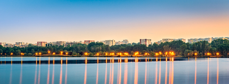 Panoramic view of Tomis Nord neighborhood skyline across Tabacariei lake, at dusk, in Constanta, Romania Banque d'images - 108371825
