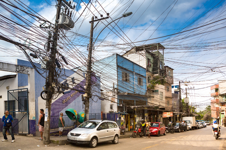 RIO DE JANEIRO - AUGUST 22, 2015: Typical street in Rochina Favela. Rocinha is the largest favela in Brazil. Messy electrical and telecom wires hang above the street. Banque d'images - 108350047
