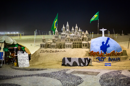 RIO DE JANEIRO - AUGUST 22, 2015: Artist and his sandcastle on Capacabana beach. The artwork represents miniatures of the main brazilian landmarks and symbols. Banque d'images - 108350048