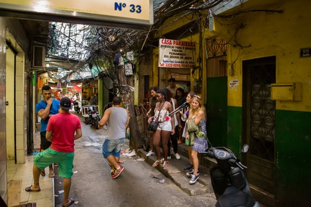 RIO DE JANEIRO - AUGUST 22, 2015: Narrow street in Rochina Favela. Rocinha is the largest favela in Brazil. Tourists and locals mingle in front of shops.