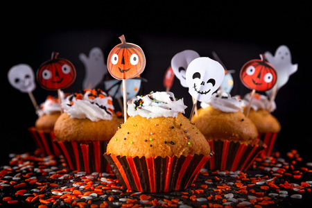 Happy Halloween muffin cupcakes with funny party decorations set against a black background with differential focus and creative lighting. Banque d'images - 108372331
