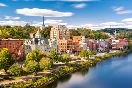 Augusta skyline on a sunny afternoon (long exposure for smooth sky and water). Augusta is the state capital of the U.S. state of Maine and the county seat of Kennebec County Banque d'images - 115066719