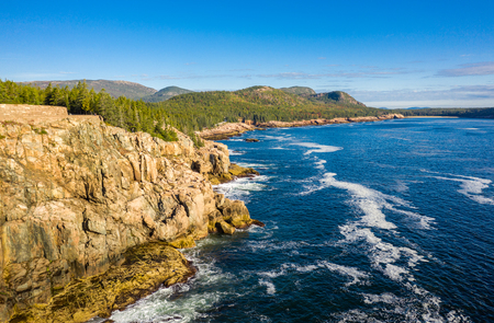 Aerial view of Acadia shore in Maine on a sunny morning with waves crashing on rocky cliffs Banque d'images - 115066771