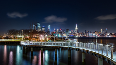 Pier C park in Hoboken, New Jersey by night, with the New York City skyline in the background.