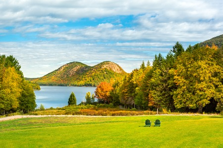 Jordan Pond and the two Bubble mountains in Acadia Nantional Park, Maine, with two empty seats on a green lawn Banque d'images - 120564148