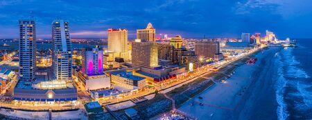 Panorama aéreo de Atlantic City a lo largo del malecón al anochecer. En la década de 1980, Atlantic City logró la atención nacional como centro de juegos de azar y actualmente cuenta con nueve grandes casinos.