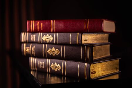 Old books stacked on a wooden desk photographed with in a dim lit study with selective focus 版權商用圖片