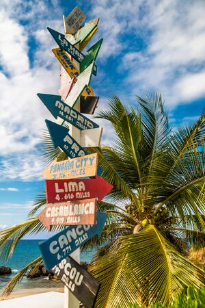 Directional sign on the beach indicating different wold destinations, photographed in the Dominican Republic.